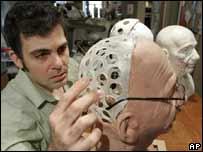 Un hombre trabaja sobre el cr�neo de acr�lico de un robot que tiene rostro humano