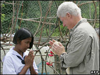 Mr Clinton receives a garland during a visit to Phuket in Thailand