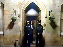 Police officers stand guard outside the Ashdown Park Hotel