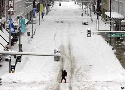 A man crosses a deserted, snow-covered street in downtown Denver