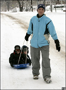 A woman pulls her two sons on a sledge in Denver