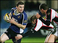 Brian O'Driscoll is about to be tackled by Paul Steinmetz with Paddy Wallace close by