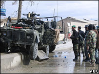 Afghan policemen stand near the damaged Nato vehicle