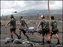 Soldiers carry a victim of the mudslides in the shadow of Mt Mayon