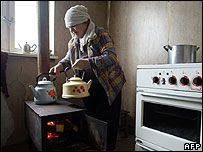 Georgian woman putting a kettle on a stove