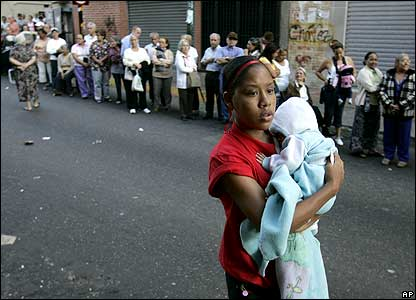 Woman carrying baby near queue