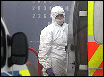 A forensic police officer in front of the container