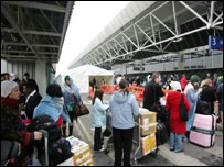 Passengers queue outside terminal four of Heathrow airport