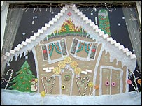 A gingerbread house in a window