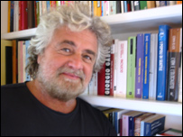 Beppe Grillo in front of his library
