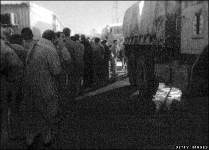 Prisoners being loaded onto trucks