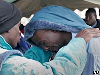 A would-be migrant from Senegal is comforted after his repatriation from Spain