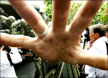 A Fijian soldier's hand blocks the camera as a truckload of around 30 soldiers arrived and cleared a large group of journalists and onlookers in front of residence of Prime Minister Laisenia Qarase