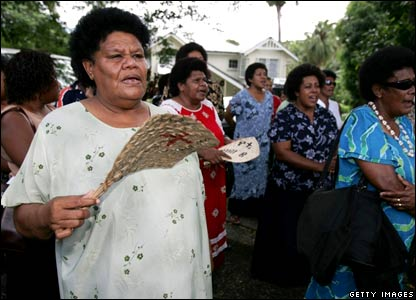A prayer group sing a song as Fijian military soldiers erect roadblocks around the home of Fijian Prime Minister Laisenia Qarase