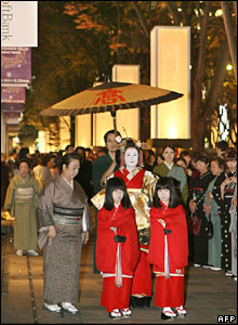 A kimono-clad tayu (high-class geisha) walks on a street featuring light towers in Tokyo's fashion district Omotesando Hills