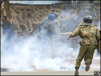 A Kenyan demonstrator, left, shields himself from tear gas as Kenyan riot police charge Kenyan protesters in Nairobi
