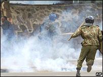 A Kenyan demonstrator, left, shields himself from tear gas as Kenyan riot police charge Kenyan protesters in Nairobi