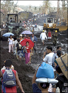 Villagers make their way on a road covered by volcanic mud and debris being cleared by bulldozers in Padang village, Legaspi city, in the Philippines