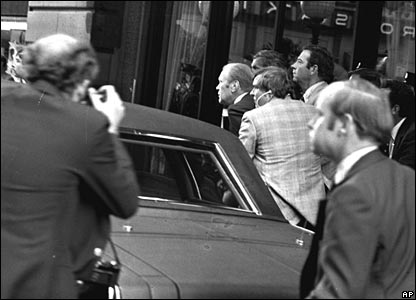 Mr Ford ducks behind his limousine after a shot was fired at him in San Francisco on 22 September 1975
