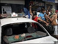Manifestantes destruyen un patrullero policial