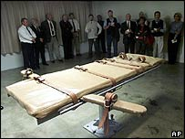 Witnesses stand around an execution gurney