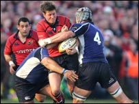 Ronan O'Gara is tackled by Stanley Wright and Trevor Hogan