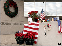 Candles, flags and flowers are placed by the Gerald R Ford Museum in Grand Rapids, Michigan