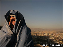 An Afghan woman in a burka stands overlooking the capital, Kabul