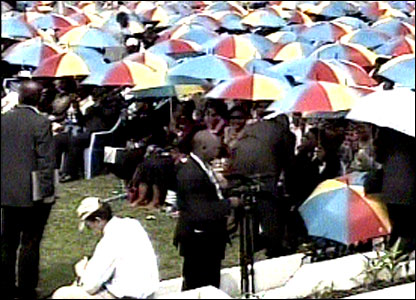 Crowds sheltering under umbrellas (Screen grab: RTNC TV)
