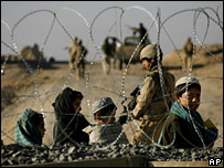 Afghan children and a Canadian soldier seen through razor wire in Kandahar