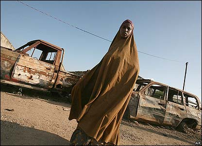 A woman walks past destroyed Islamic courts vehicles in Burhakaba