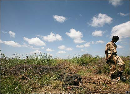 Somali soldier walks through a field past a dead Islamist fighter