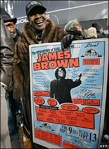 Elizabeth Gordon holds up a poster of James Brown outside the Apollo Theater in Harlem