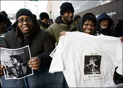 Cheese Fletcher and Brenda Harper hold up James Brown memorabilia outside the Apollo theatre in Harlem