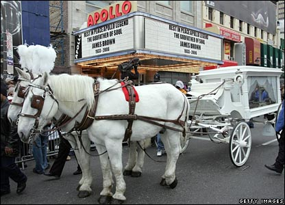 A horse drawn carriage carrying the casket of James Brown