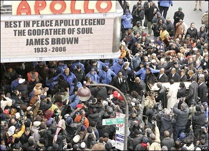 Pall bearers carry the casket with James Brown's body into the Apollo Theater