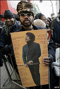 A fan lines up outside the Apollo Theater to view the body of James Brown