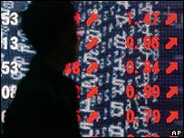 Man passes electronic board showing Japanese share prices