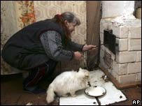 Woman stoking oil stove in Belarus
