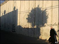 Palestinian woman walks near Israeli wall in West Bank