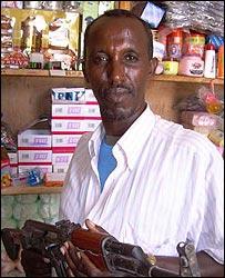 Shopkeeper Ahmed Sa'id Ali in Mogadishu holding a gun