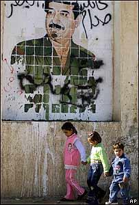 Niños iraquíes pasan delante de un cartel donde se ve a Saddam sonriente