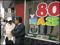"Two men standing by a sign saying ""80 and more"""