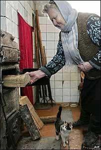Un abuela en Minsk mete leños en la estufa, para quitarse el frío