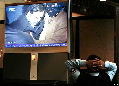 Iraqi policeman watching execution footage on TV