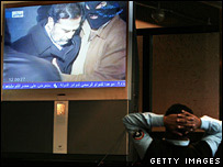 A man watching footage of Saddam Hussein's execution