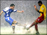 Wigan's Leighton Baines (left) and Watford's Ashley Young battle for the ball in the heavy rain