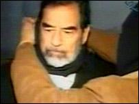 الرئيس العراقي السابق صدام حسين وشخص ملثم يلف حول عنقه عصابة سوداء ثم حبل المشنقة