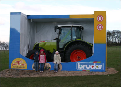 """Children with """"life-size toy tractor"""""""