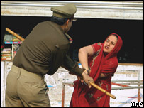 A relative struggles with a policeman outside the house in New Delhi.